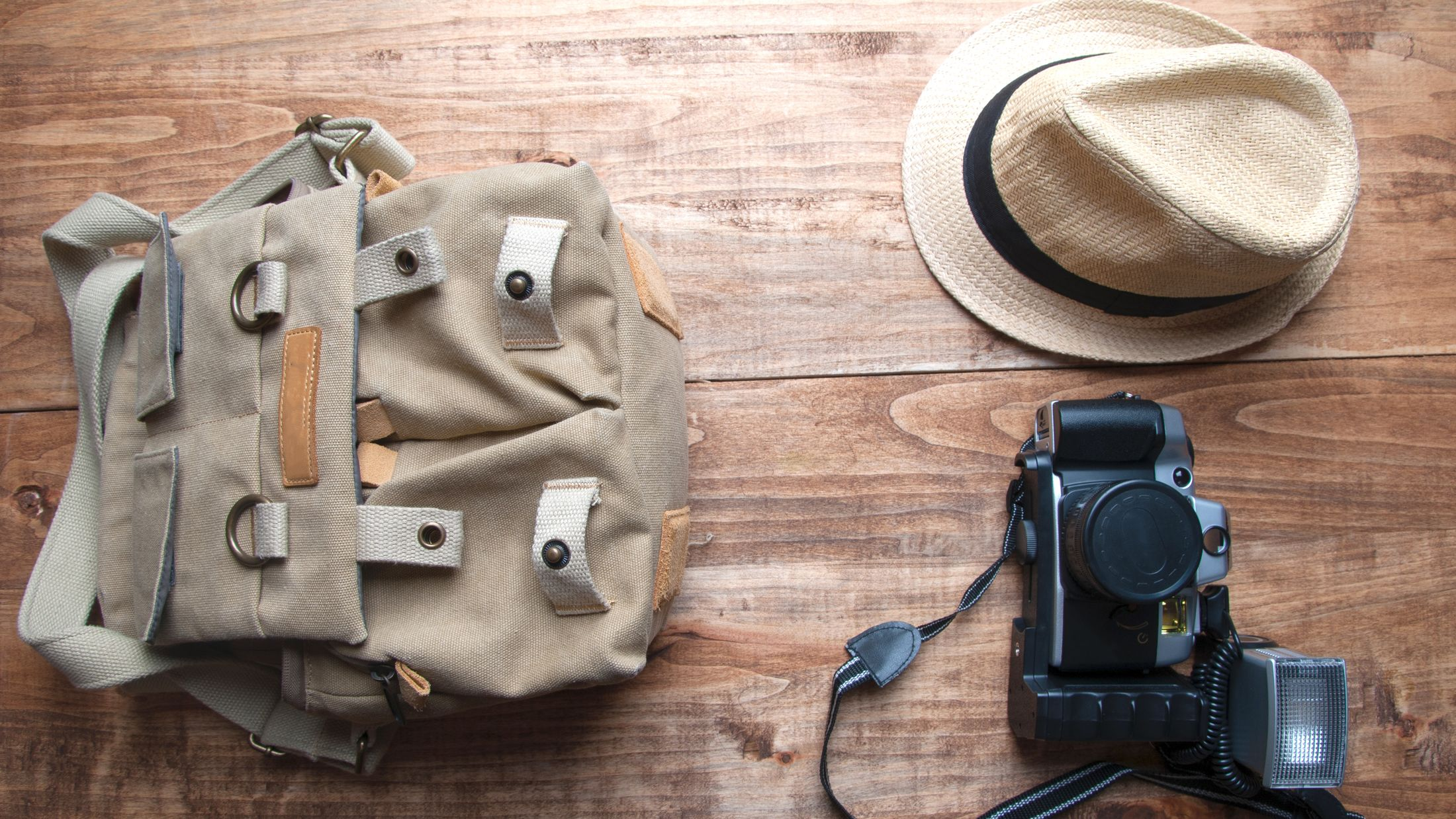 Tourism concept. Backpack, hat , binocular and old camera isolated on wooden background.; Shutterstock ID 437880175; PO: Project Italy - Facilities images; Job: Project Italy - Facilities images; Client: H&J/Citalia