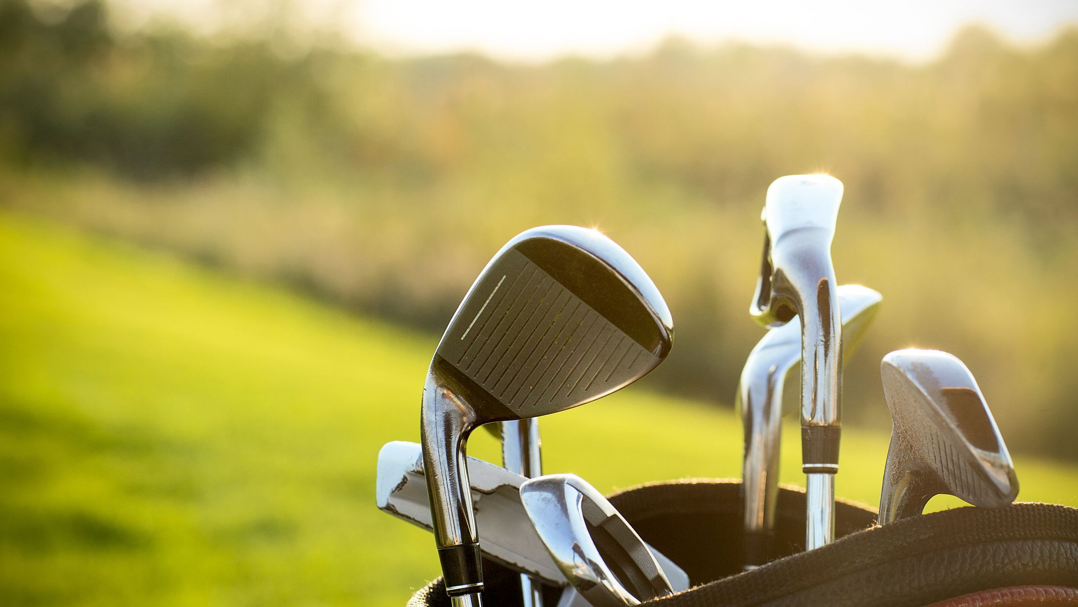 Golf clubs drivers over green field background. Summer sunset; Shutterstock ID 255601300; PO: Project Italy - Facilities images; Job: Project Italy - Facilities images; Client: H&J/Citalia