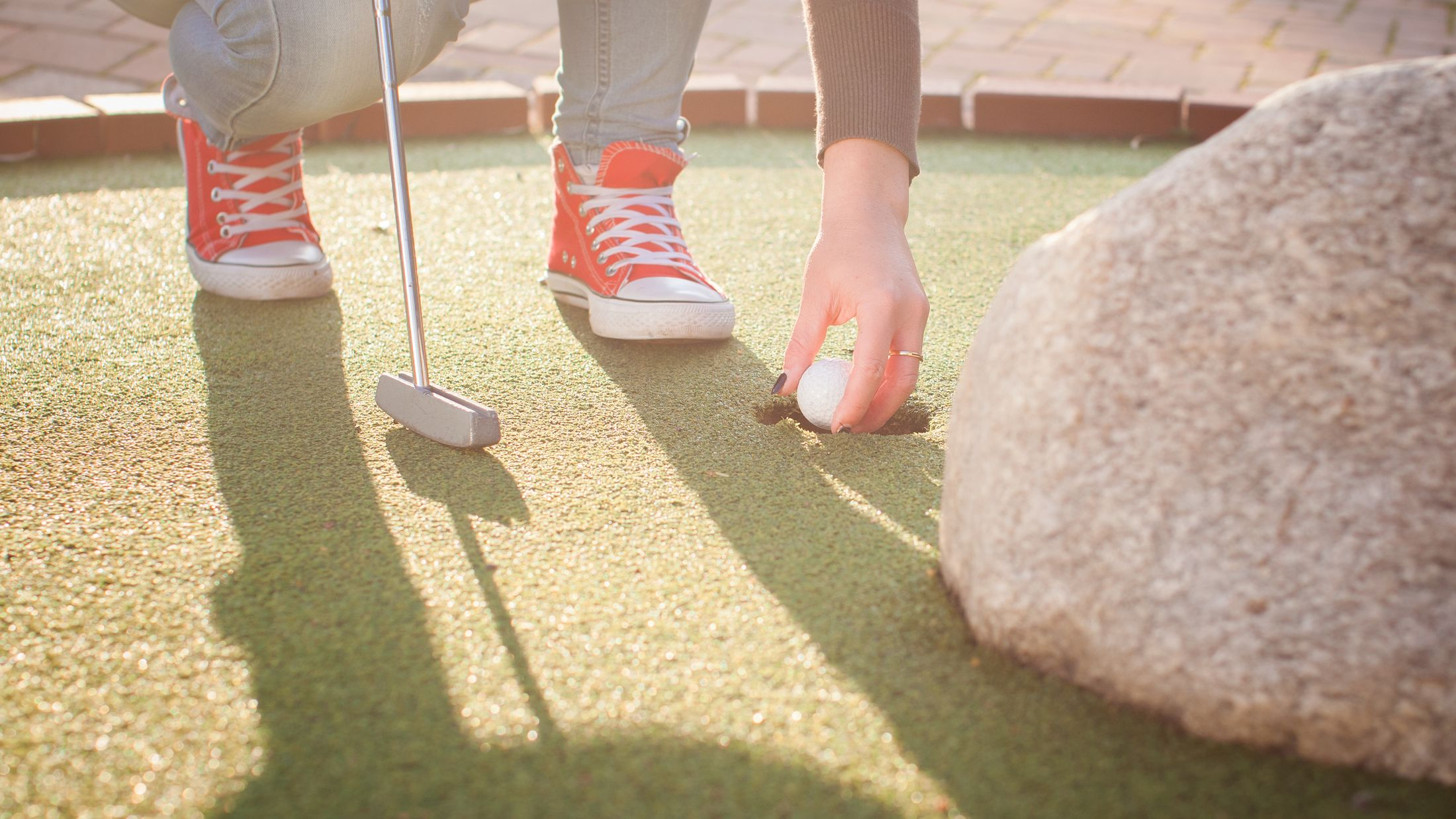 Detail of young woman playing mini/adventure golf on a beautiful sunny summer day (colorful image, photo was taken in warm evening light); Shutterstock ID 219627934; PO: Project Italy - Facilities images; Job: Project Italy - Facilities images; Client: H&J/Citalia